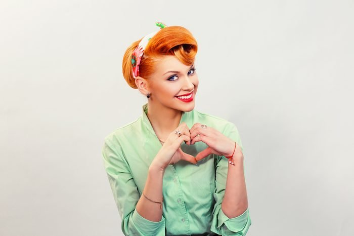 Closeup portrait smiling cheerful happy young pin up woman making heart sign with hands isolated grey wall background. Positive human emotion expression feeling life perception attitude body language