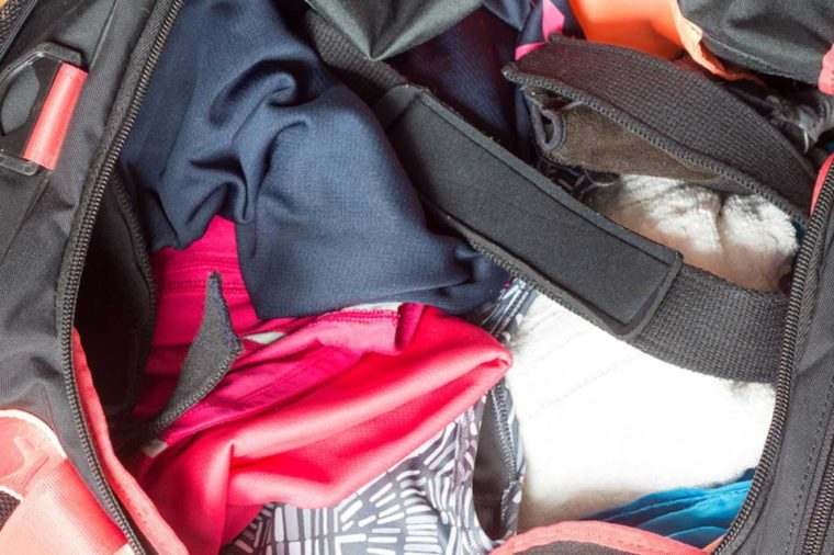 Top view of the inside of the girl's gym bag containing sports equipments such as clothes, towel and wrist strap