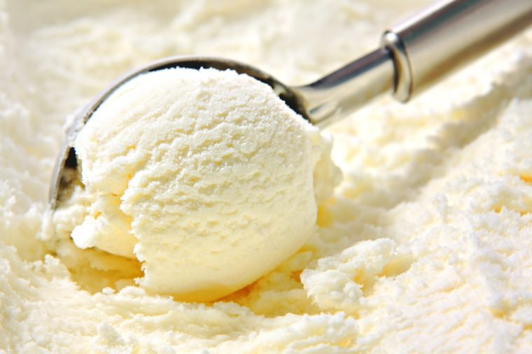 Vanilla ice cream scoop, scooped out of a container with a utensil