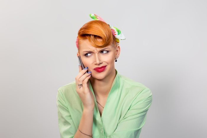 Frustrated woman on cell phone. Closeup portrait headshot beautiful angry unhappy mad serious girl student talking on mobile grey gray wall background Multicultural mixt race Pinup retro vintage model