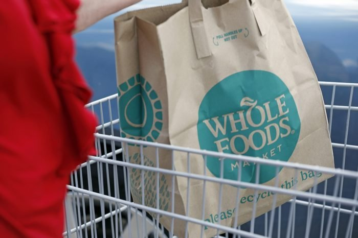 A Whole Foods Market customer carries her purchase from the Jackson, Miss., store . Amazon is buying Whole Foods Market in a deal valued at $13.7 billion, uniting the on-line giant with the grocery store chain that touts fresh organic foods
