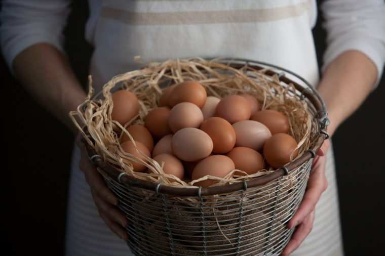 Woman Holding Wire Basket of Fresh Chicken Eggs Horizontal