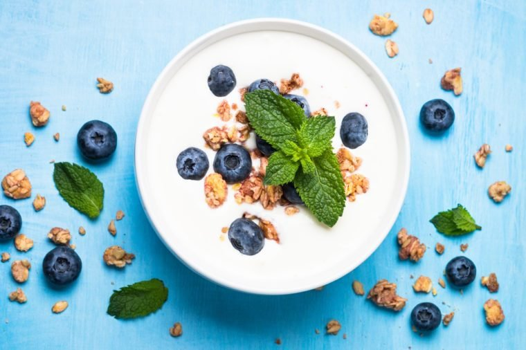 Greek yogurt granola and blueberries on blue table top view. Healthy food nutrition, snack or breakfast.