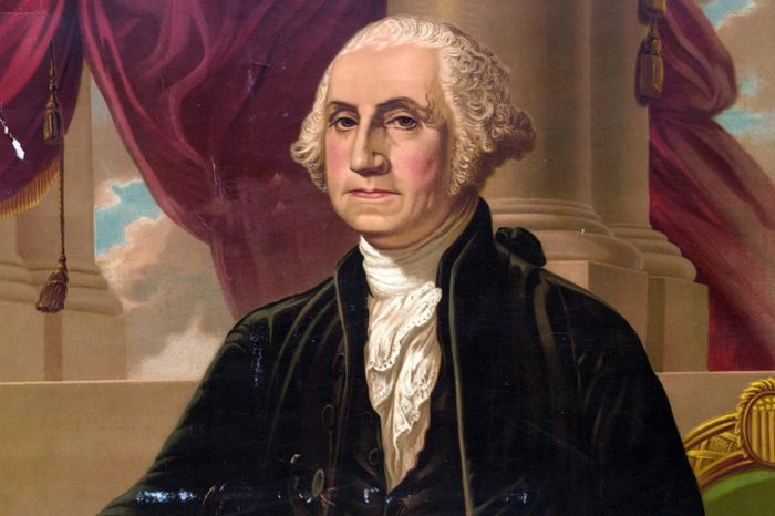 George Washington. Print showing George Washington, standing in front of a chair with right arm extended toward a table on the left and holding a sword in left hand.