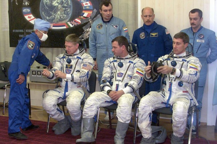 Baikonur Kazakhstan: Commander of the First Long-duration Mission to the International Space Station American Astronaut Bill Shepherd (l) Russian Cosmonauts Yuri Gidzenko (c) and Sergei Krikalev (r) Check the Space Suits As the Back Up Pilots and the Members of the 3-rd Mission at the Same Time Mikhail Tiurin (up L) American Astronaut Kenneth Bauersocks (up C) and Vladimir Dezhurov (up L) Look on Before Thestart the First Long-duration Mission to the International Space Station 31 October 2000
