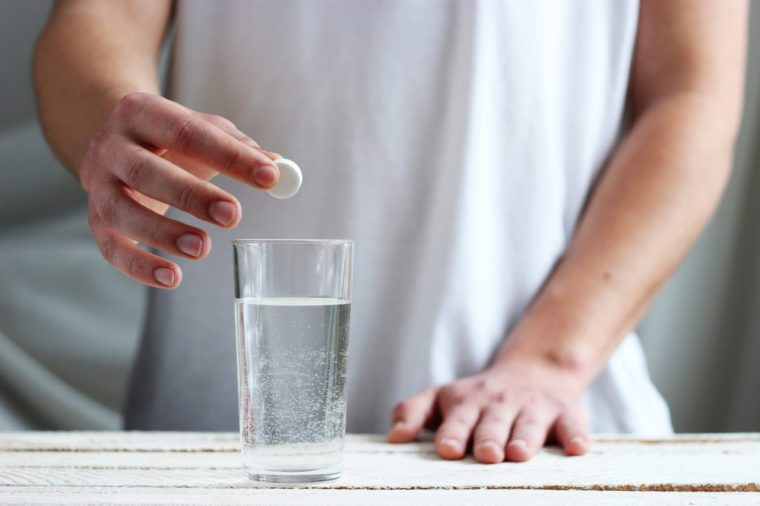 man's hands lay white tablet in a glass of water on a light background. The concept of health.