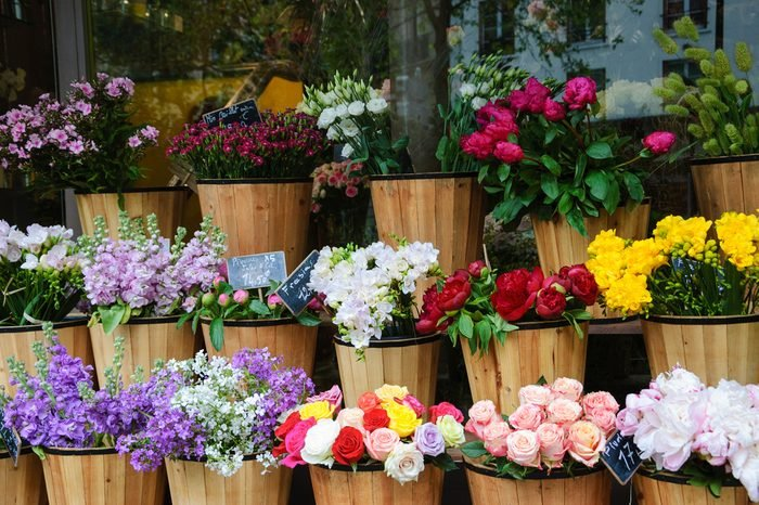 Colorful peony, roses and other flowers at the entry to flower shop in Paris (France). Selective focus.