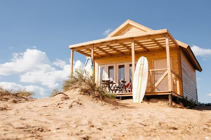 Holiday house on the beach. Wooden house with boards for wind serfing on a sand beach. Summer vacation concept.