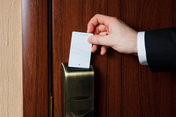 Man's hand in black suit inserts card to open electronic lock in hotel door