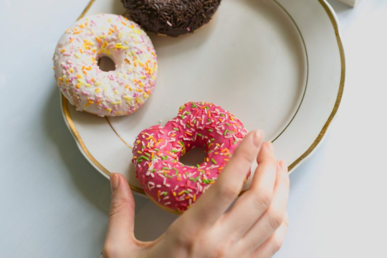 A girl's hand takes a donut from a plate with a pink chocolate frosting. View from above