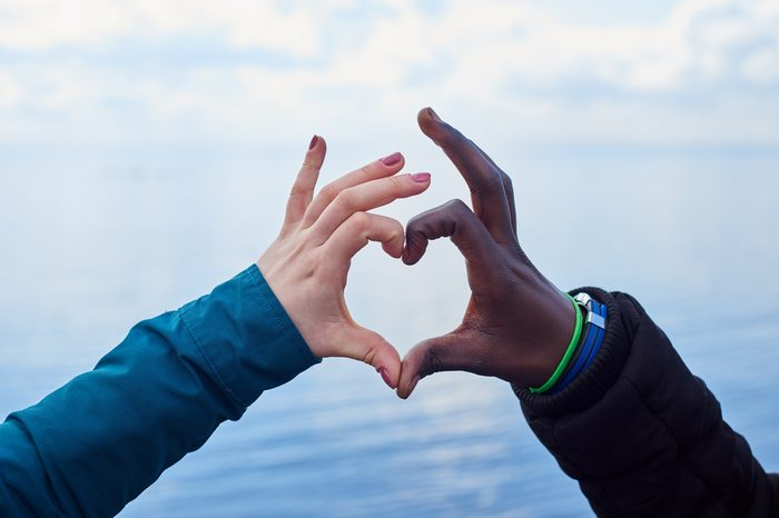 Sign of Love . White and black hands make heart symbol