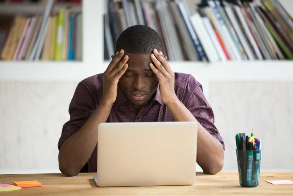 Frustrated black man feeling depressed after fail, upset african-american businessman sitting in front of laptop stressed about bankruptcy debt, dark-skinned guy suffering from headache migraine