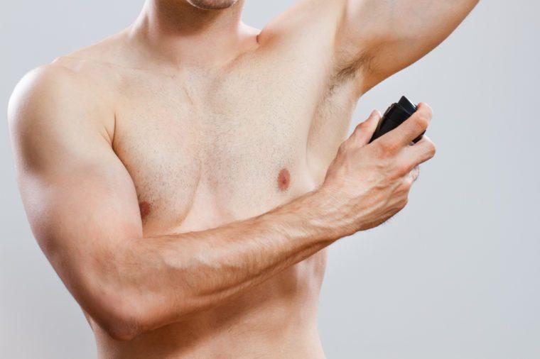 Photo of handsome man using deodorant,Man using deodorant