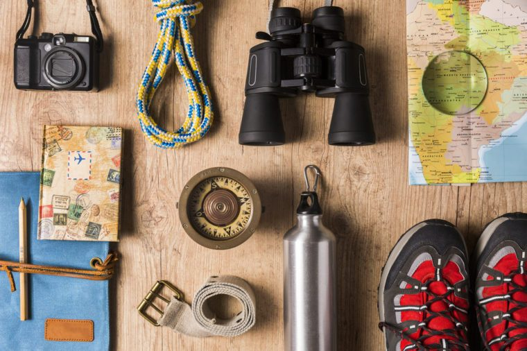 Overhead view of travel equipment for a backpacking trip on wooden floor. / Items include rope, belt, canteen, compass, map, camera, binoculars, journal, boots. Time to travel concept.