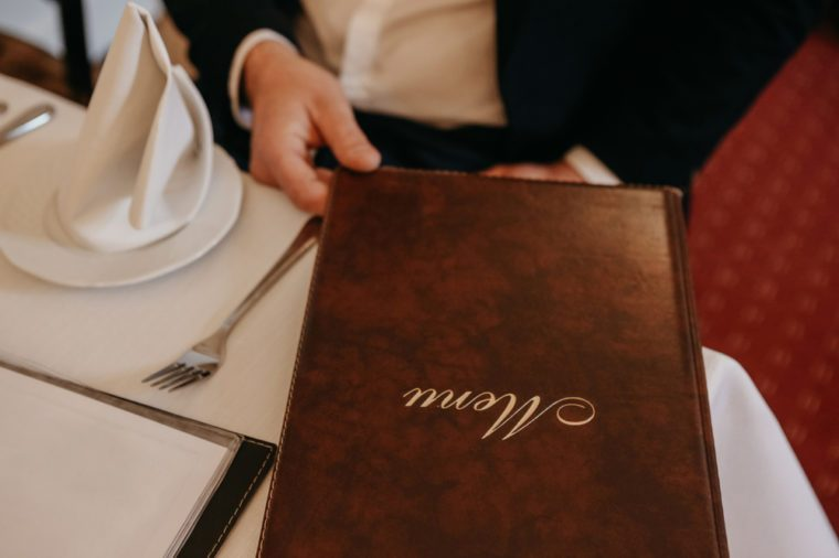 Man in restaurant reading the menu