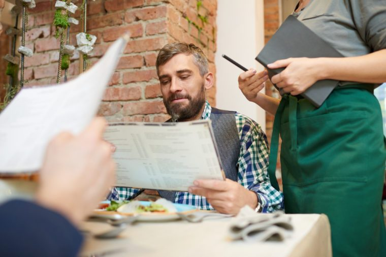 Portrait shot of bearded middle-aged man studying menu while unrecognizable waitress standing next to him and waiting for his order, interior of stylish restaurant on background