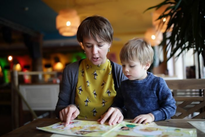 Mother with her son choosing dishes at table in the restaurant