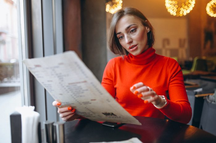 Woman in a cafe picking on the menu
