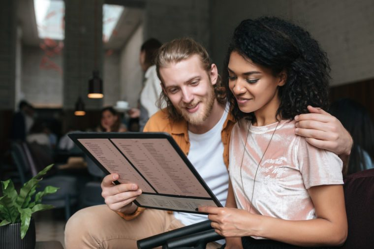 Portrait of young beautiful couple sitting in restaurant with menu in hands. Nice African American girl with dark curly hair and boy with blond hair happily looking in menu at cafe