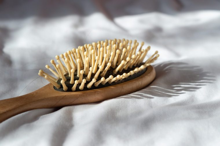 Hair fall, Hair loss problem. Wooden brown comb with hair loss on white bed cover. Woman healthy and beauty concept.