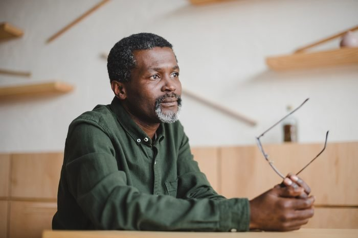 thoughtful mature african american man sitting in cafe