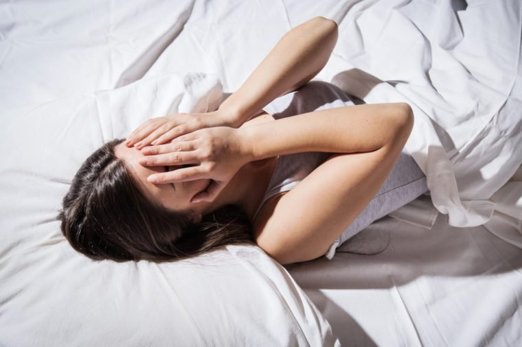 Depressed insomnia woman cover her face in bed.