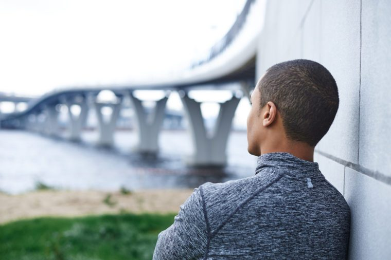 Rear view of thoughtful African American male runner in stylish sports jacket leaning on wall outdoors, looking into distance at sea, relaxing mind or meditating after running exercise in the morning