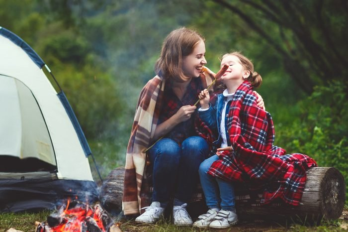 Happy tourist family on a journey hike. mother and child fry sausages on bonfire near the tent