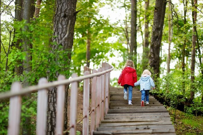 Two little sisters walking up stairs in summer park on beautiful sunny day