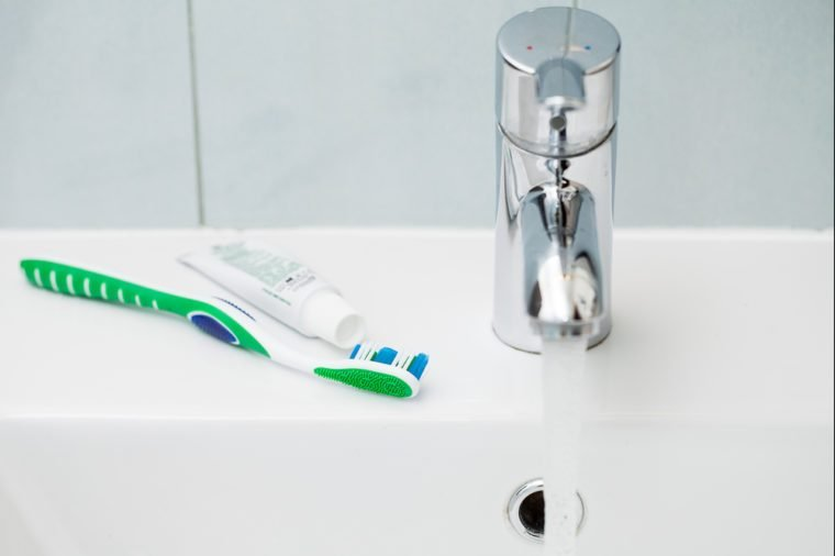 Tap and toothbrush over the clean white sink