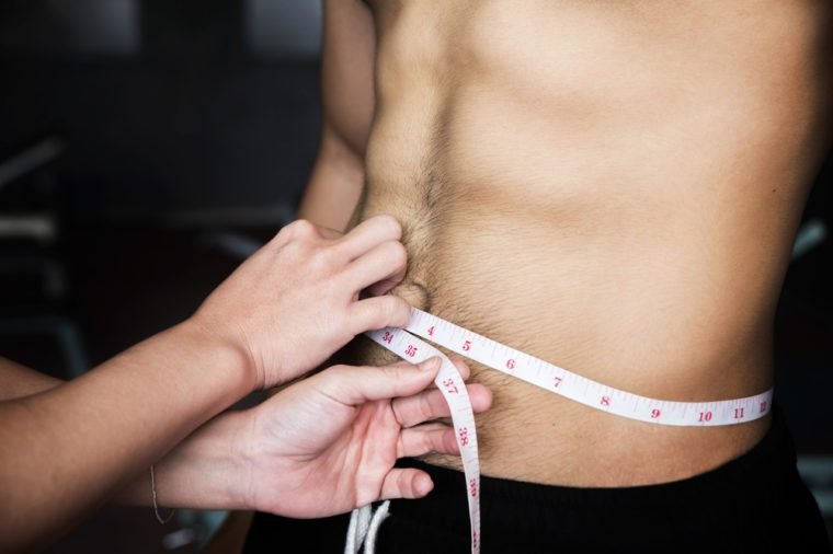 Close up hands women measure men's waist with tape measure at the gym.