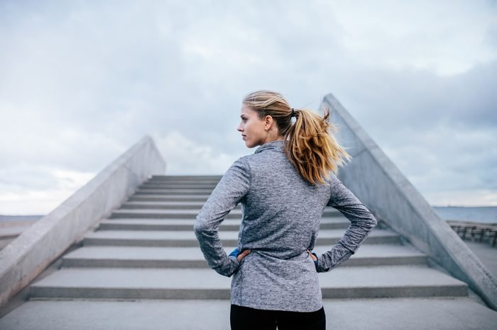 Outdoor shot of young woman standing by a stairs and looking away. Fitness female before a run.