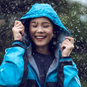 Asian woman wearing a raincoat outdoors. She is happy.