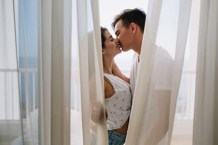 Graceful girl in white tank-top gently kissing her brunette boyfriend hiding behind light curtains. Portait of romantic young couple spending time together on balcony enjoying each other.