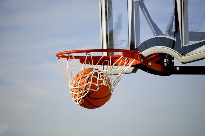 Action shot of basketball going through basketball hoop and net