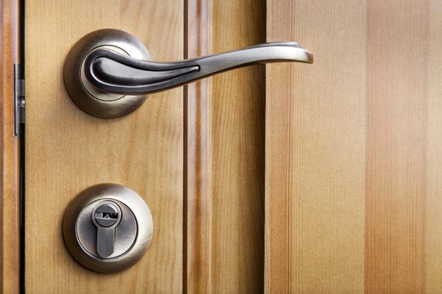 Modern style door handle on natural wooden door