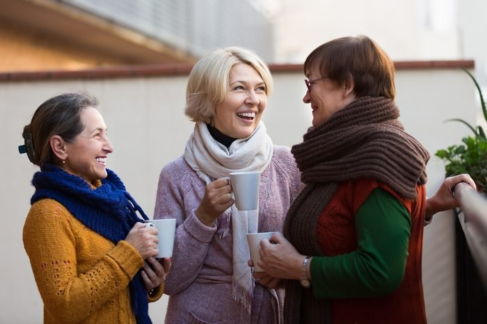 Portrait of cheerful senior female friends drinking coffee at patio. Focus on blonde