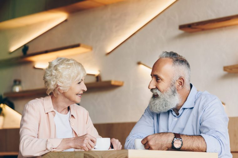 side view of senior couple having conversation while drinking coffee together in cafe