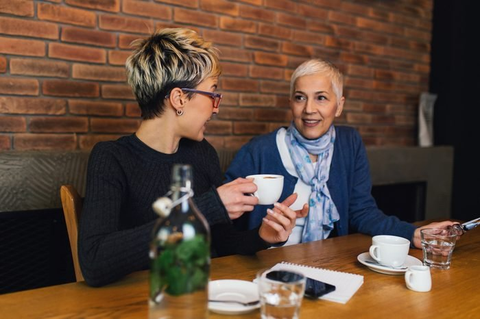 Senior mother sitting in cafe bar or restaurant with her middle age daughter and enjoying in conversation.