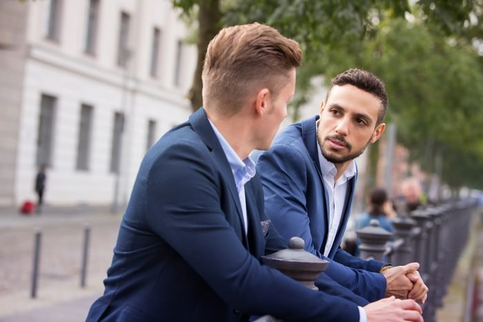 two handsome businessmen standing outside and having a conversation