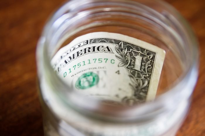 One dollar note in glass jar.Paper US dollar note savings in bank.Save money idea.Start saving currency.Finance & savings concept.National American paper currency in jar.Save dollars notes for future