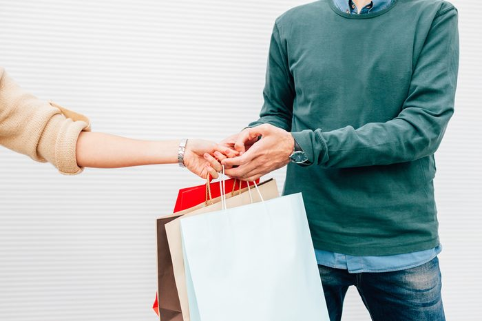 Closeup of man giving his wife gift in shopping bags