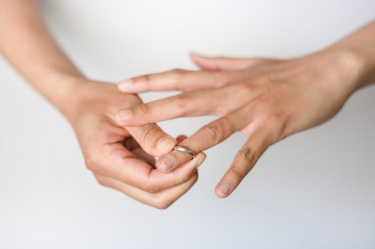 A woman is taking off her wedding ring from her finger.