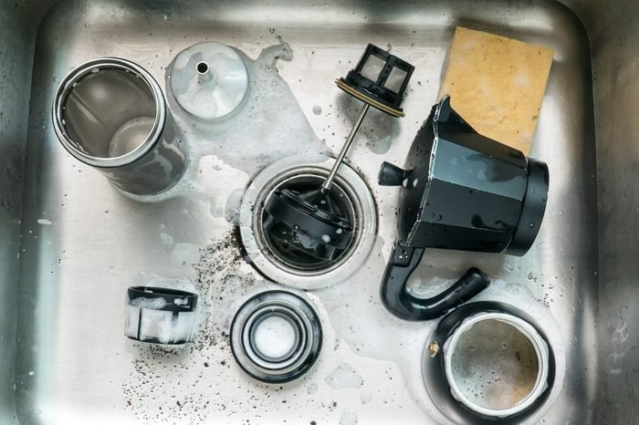 Black Mocca pot and France press coffee maker parts in stainless steel cleaning sink with sponge and white bubbles.