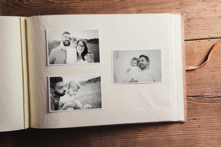 Fathers day composition - photo album with a black and white photos. Studio shot on wooden background.