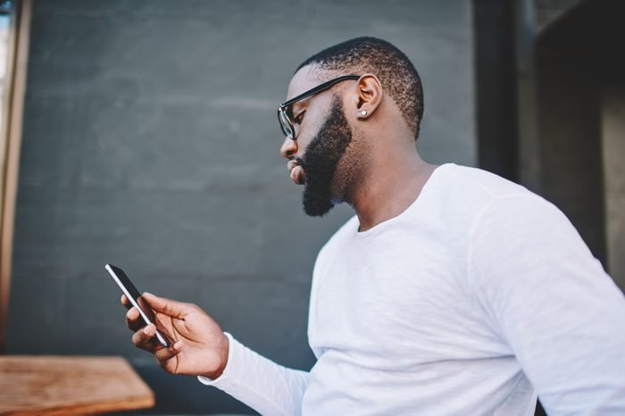 Side view of handsome african american guy reading message on phone while standing outdoors in, dark-skinned hipster in shirt with copy space for brand name or label installing application on mobile