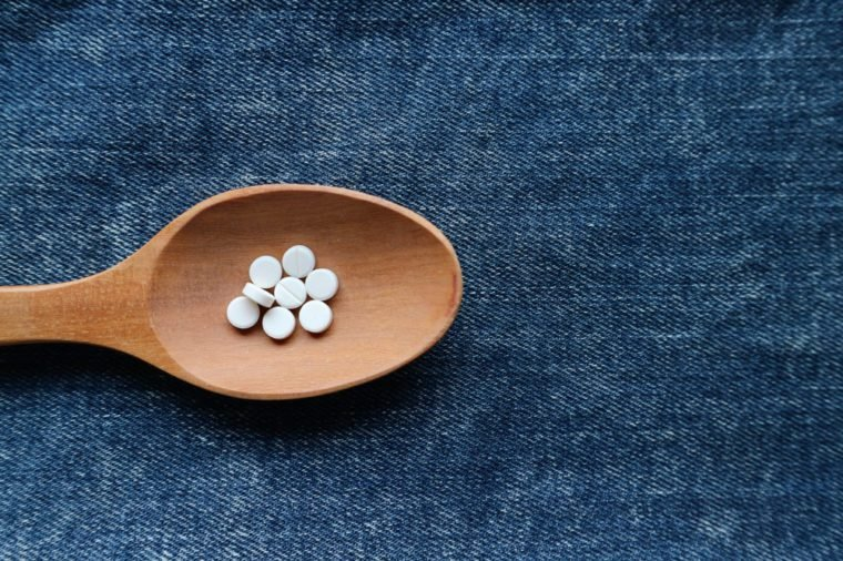 White round pills medicine on wood spoon on blue jeans denim background with empty space