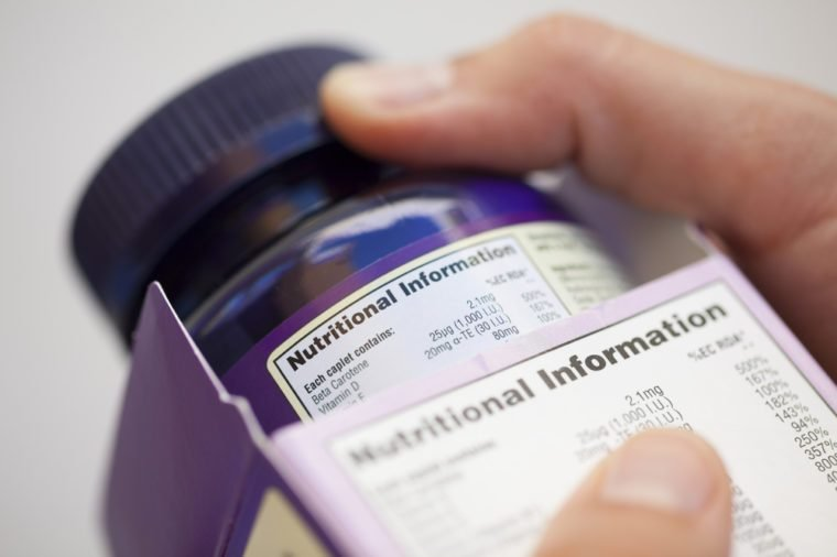 Human hand take out bottle with vitamin pills from the box for reading Nutritional information.