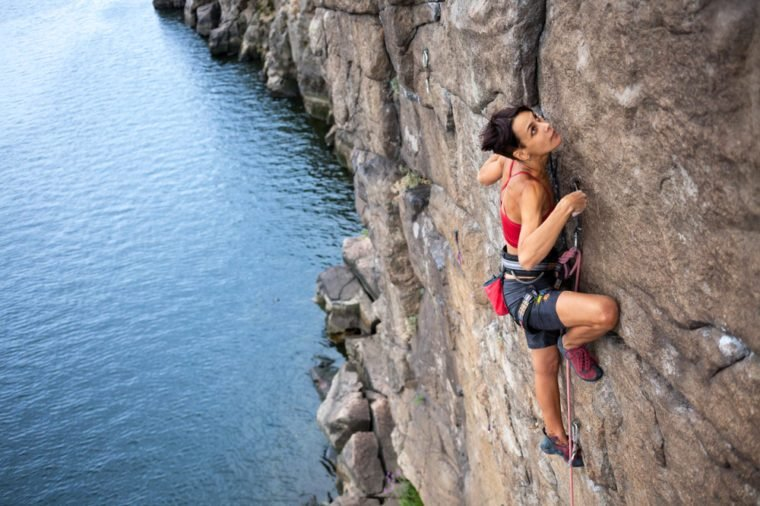 The girl climbs a climbing route over the water. extreme travel. Sport in nature.