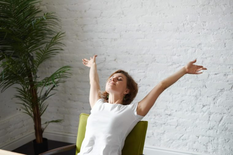 People, work, leisure and relaxation concept. Indoor shot of beautiful woman freelancer reclining on chair, raising arms in the air while stretching after hard working day at her home office
